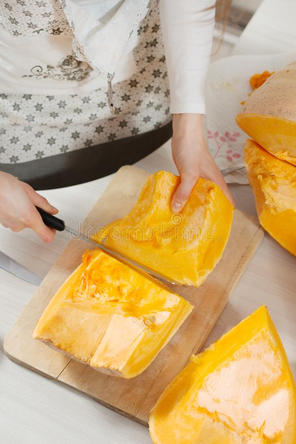 Pumpkin in large pieces lies on a chopping board. Female hands hold a long kitchen knife and cut the pumpkin into smaller pieces. Pumpkin in large pieces lies stock image