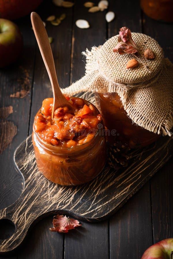 Pumpkin, lemon and apricot kernel jam. Pumpkin jam on a dark rustic background. Autumn harvest. Cozy autumn still life. Homemade preparations for the winter stock images