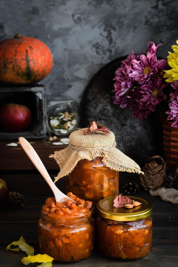Pumpkin, lemon and apricot kernel jam. Pumpkin jam on a dark rustic background. Autumn harvest. Cozy autumn still life. Homemade preparations for the winter royalty free stock image