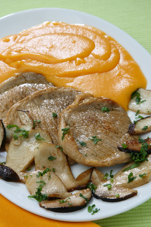 Pumpkin mash with roast meat and mushrooms stock photo