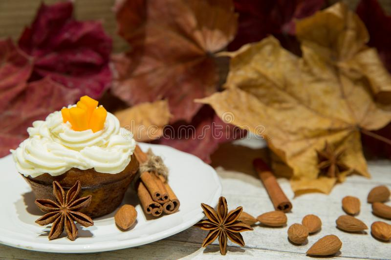 Pumpkin muffin with spices and nuts, decorated with pumpkin strips, whiped cream cheese and dried autumn leaves, yellow, red and stock photography