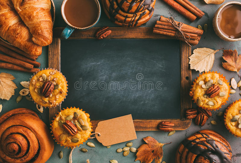 Pumpkin muffins and cinnamon rolls and coffee. royalty free stock photography