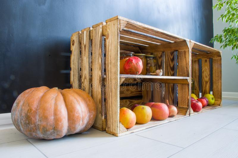 Pumpkin next to wooden box filled with fruit and preservation on floor in modern kitchen on background of black wall. Autumn harve. St supplies for winter stock photos