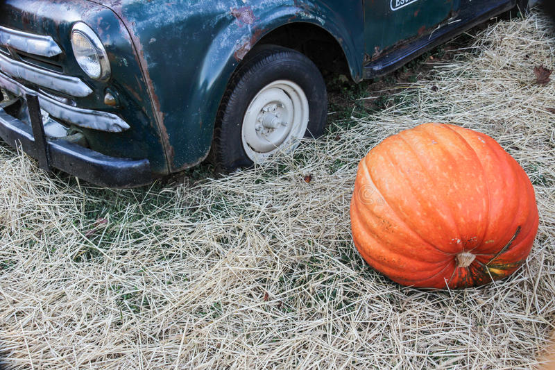 Pumpkin and old truck in hay royalty free stock photography