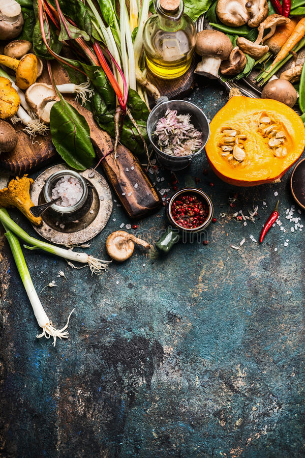 Pumpkin and Other autumn vegetables and seasoning ingredients for seasonal cooking on rustic kitchen table background royalty free stock photo