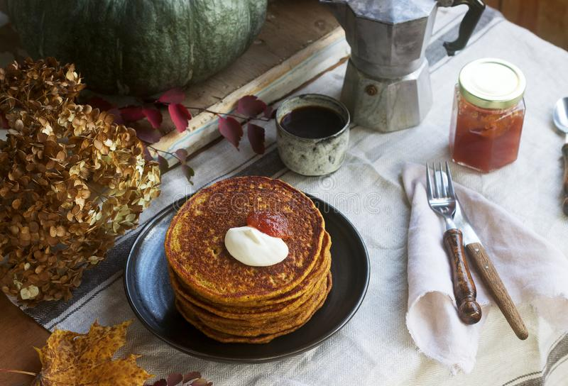 Pumpkin pancakes with cream and jam on a background of autumn still life stock photo