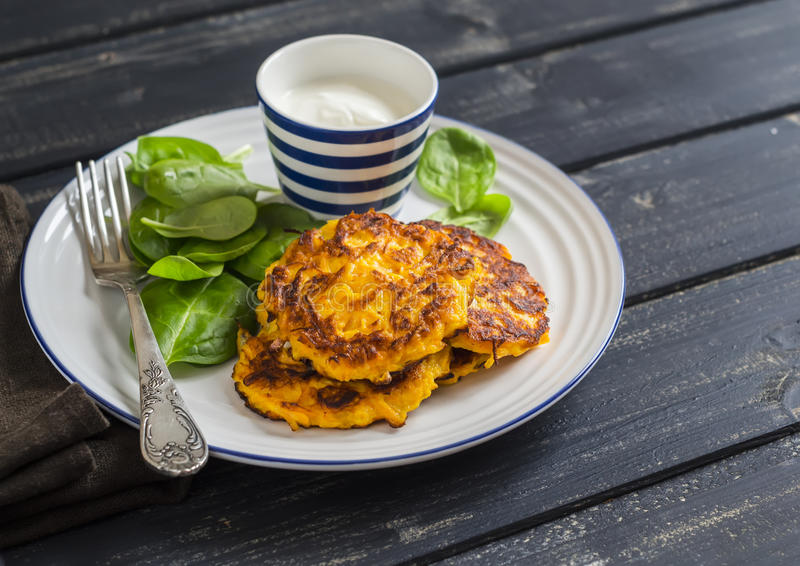 Pumpkin pancakes and fresh spinach. royalty free stock photography