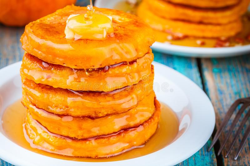 Pumpkin pancakes with honey and butter. On wooden table stock photos