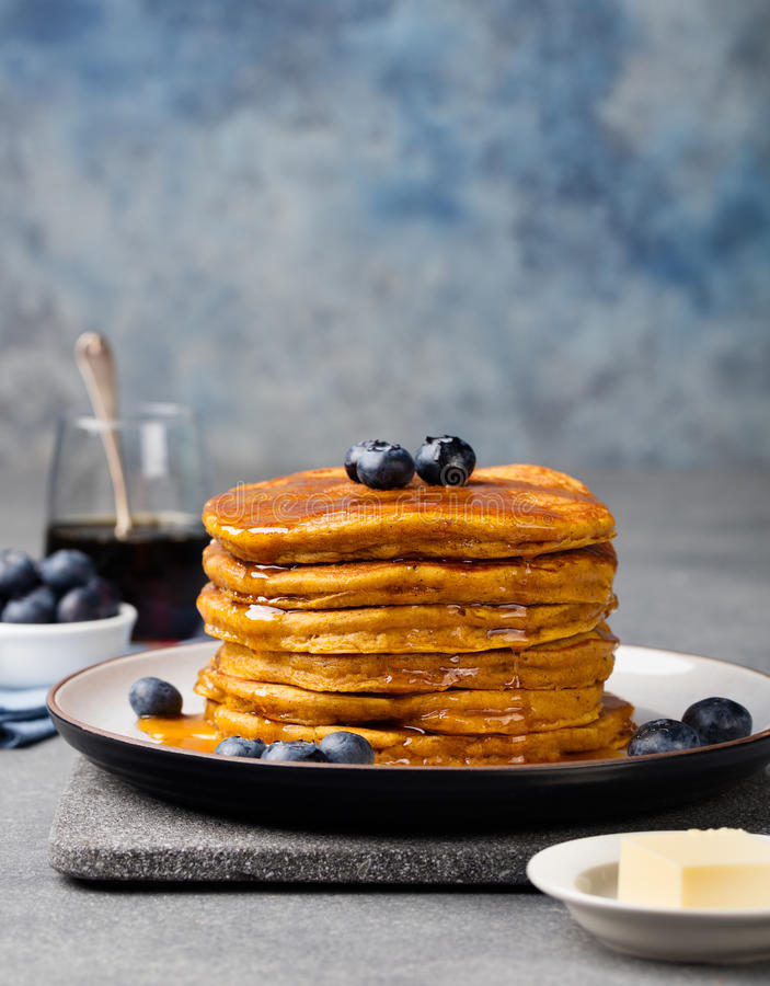 Pumpkin pancakes with maple syrup and blueberries on a plate. Grey stone background.  royalty free stock photos