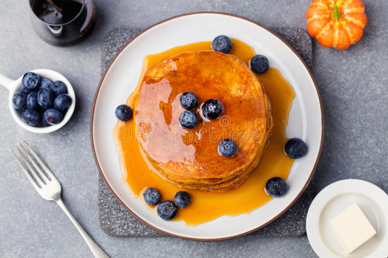 Pumpkin pancakes with maple syrup and blueberries on a plate Grey stone background Top view. Pumpkin pancakes with maple syrup and blueberries on a plate. Grey stock photos