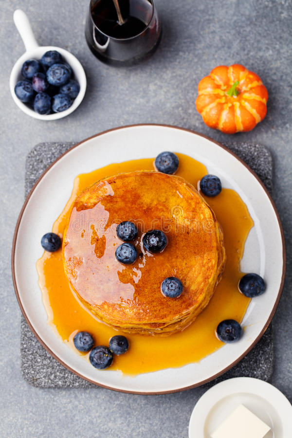 Pumpkin pancakes with maple syrup Top view. Pumpkin pancakes with maple syrup and blueberries on a plate. Grey stone background Top view stock photo