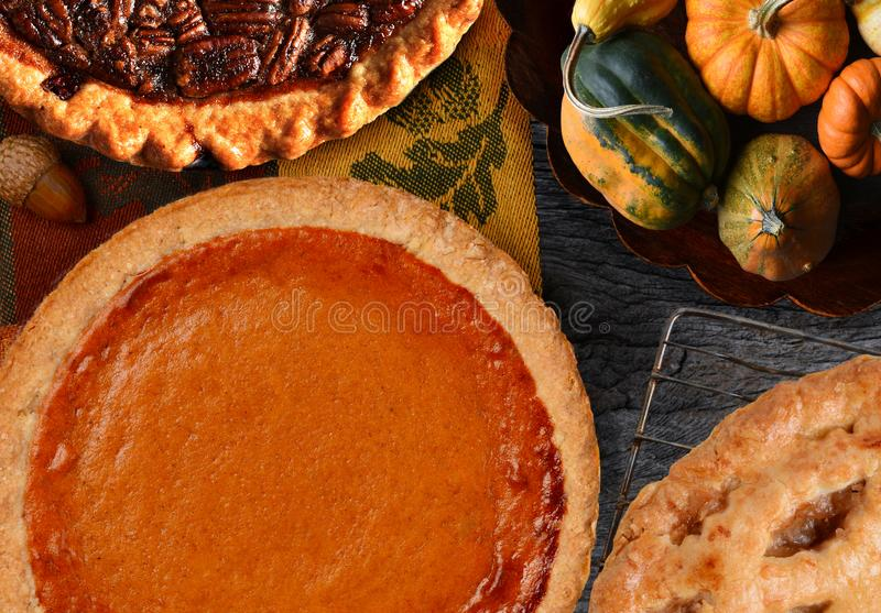 Pumpkin, Pecan and Apple Pies for Thanksgiving. With a bowl of decorative gourds stock image