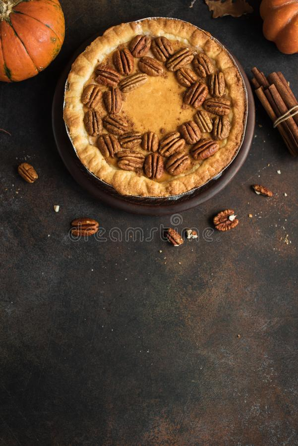 Pumpkin Pecan Pie. Pumpkin and Pecan Pie with cinnamon on rustic background, top view, copy space. Homemade autumn pastry for Thanksgiving stock image