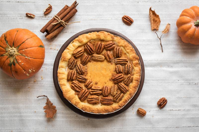 Pumpkin Pecan Pie. Pumpkin and Pecan Pie with cinnamon on white linen background, top view, copy space. Homemade autumn pastry for Thanksgiving royalty free stock photography