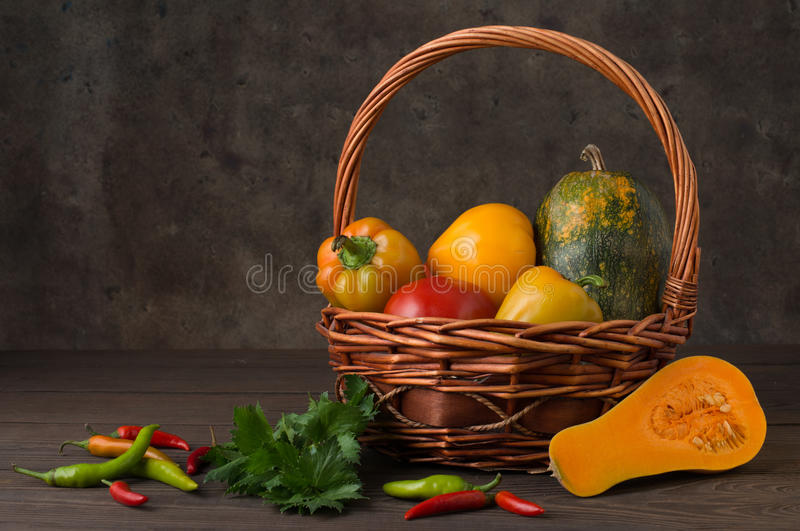 Pumpkin pepper tomato in a basket on a background of pepper and pumpkin royalty free stock image