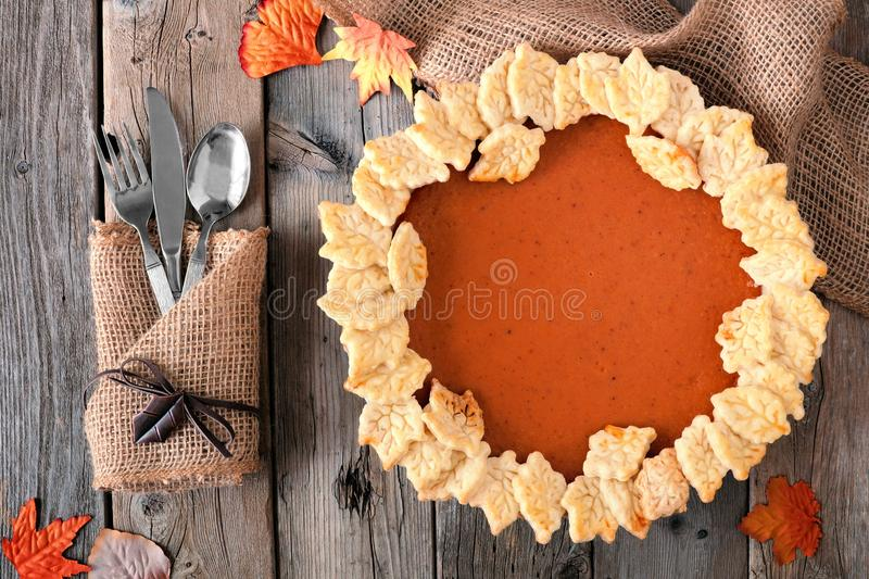 Pumpkin pie with autumn leaf pastry design, overhead table scene royalty free stock images