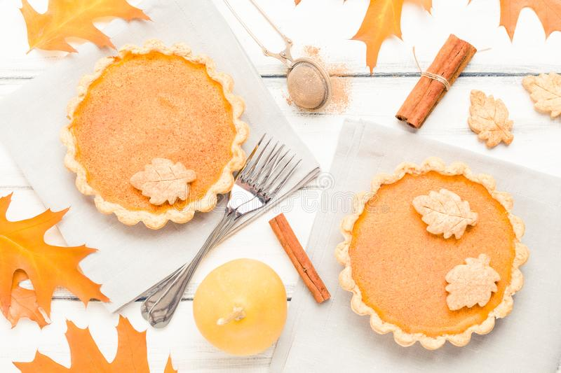 Pumpkin pie with cinnamon and cookies on gray napkins on white wooden background with autumn yellow leaves. stock photography