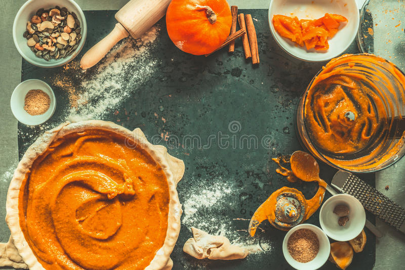 Pumpkin pie preparation with ingredients and kitchen tools on dark rustic background, top view, frame. royalty free stock photos