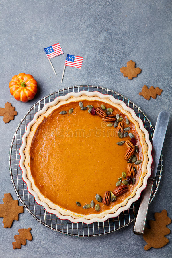 Pumpkin pie, tart made for Thanksgiving day with American flag Grey stone background. Top view. stock image