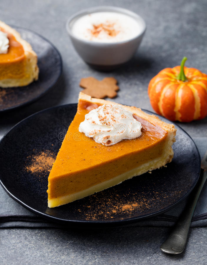 Pumpkin pie, tart made for Thanksgiving day on a black plate. Grey stone background. royalty free stock photography