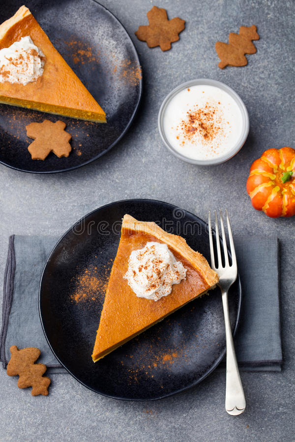 Pumpkin pie, tart made for Thanksgiving day with on a black plate. Grey stone background Top view stock image