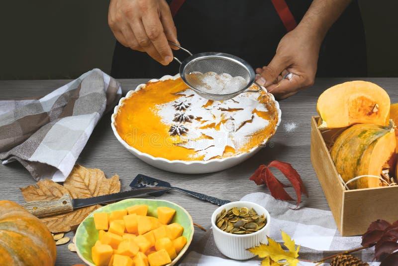 Pumpkin pie, tart made for Thanksgiving day. Fresh round bright orange homemade pumpkin pie in baking dish stock photos