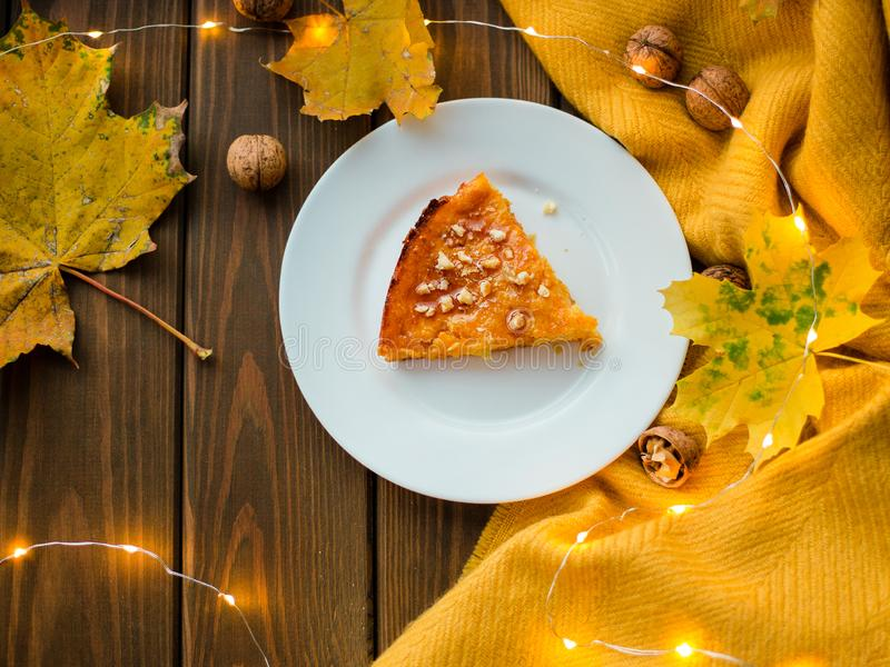 Pumpkin pie, tart made for Thanksgiving day with nuts on a white plate.Wood background Top view royalty free stock photography