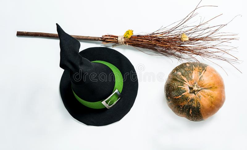 A pumpkin, a pointed Magic hat with a green ribbon and a silver buckle, a witch`s broom on a white background. In isolation. stock photos