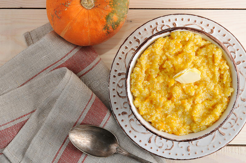 Pumpkin porridge with butter and a pumpkin. On wooden background with Cutlery - top view stock image