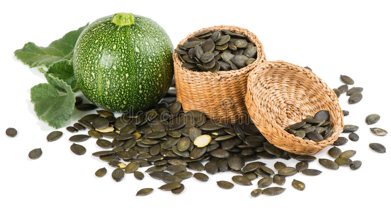 Pumpkin with pumpkin seeds in a basket. Pumpkin seeds in a wicker basket and pumpkins with leaves on white royalty free stock images