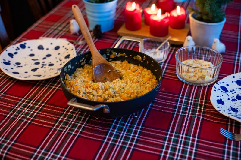 Pumpkin risotto served with pan on dining table royalty free stock image