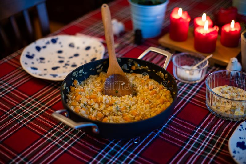 Pumpkin risotto served with pan on dining table stock photo