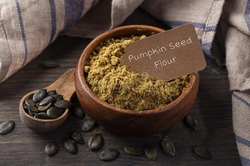 Pumpkin seed flour in a wooden spoon royalty free stock photos