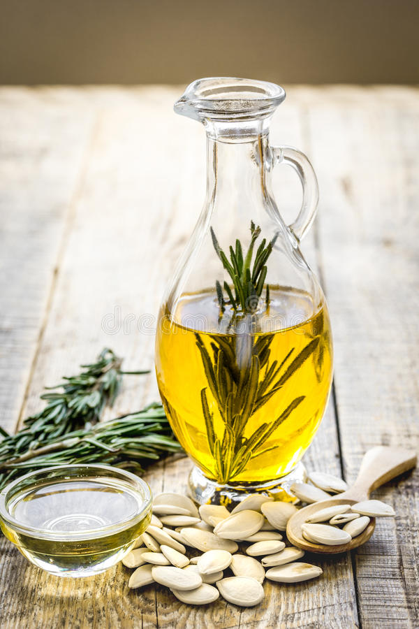 Pumpkin seed oil with ingredients on kitchen table background royalty free stock photo