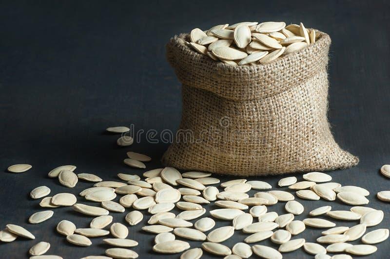 Pumpkin seeds in burlap sack or sackcloth on black wooden vintage rustic backdrop royalty free stock image