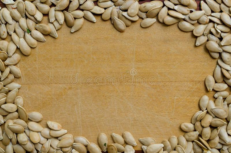 Pumpkin seeds forming a closed area on a wooden surface. frame.  stock photography