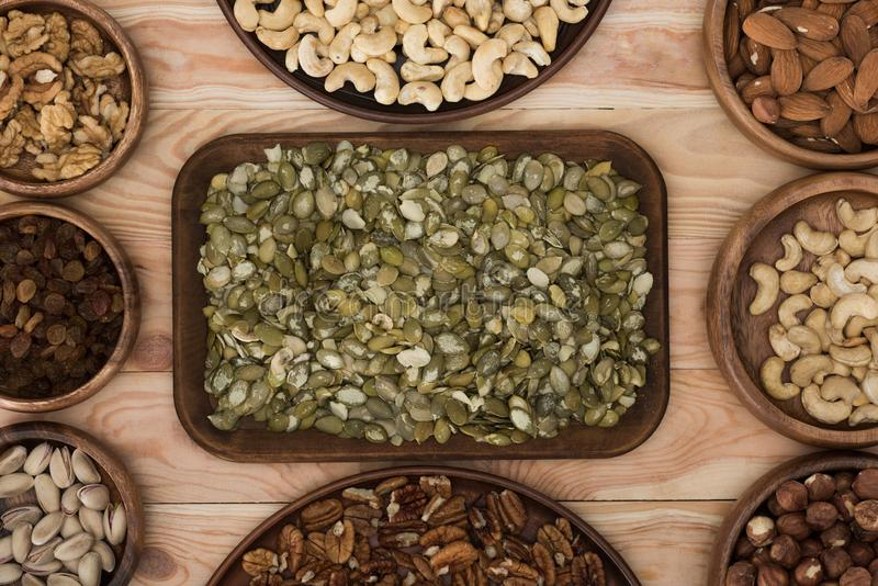 Pumpkin seeds and nuts. Top view of pumpkin seeds, raisins and various nuts on wooden table royalty free stock photos