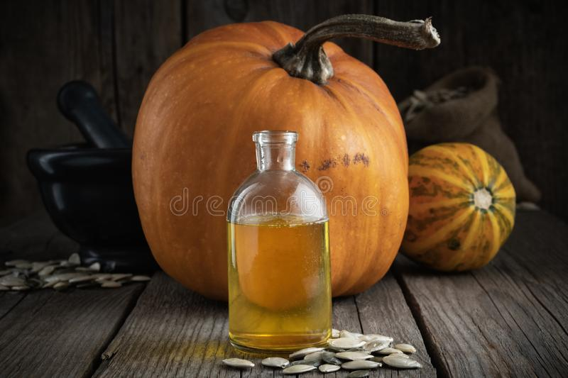 Pumpkin seeds oil bottle closeup, two pumpkins, bag of seeds and mortar on background. Pumpkin seeds oil bottle closeup, two pumpkins, bag of seeds and black royalty free stock photography