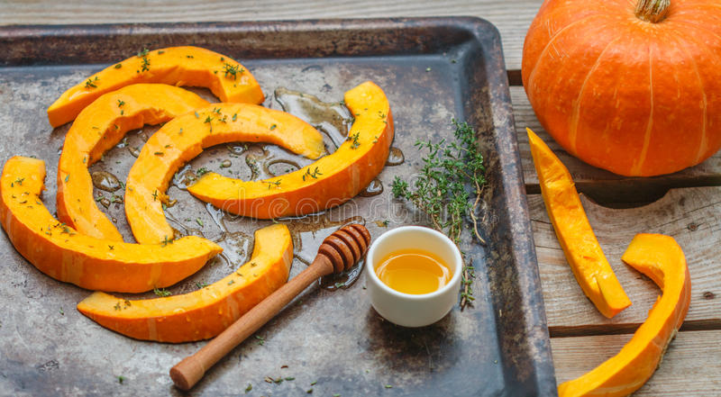 Pumpkin slices for baking with thyme and honey stock images