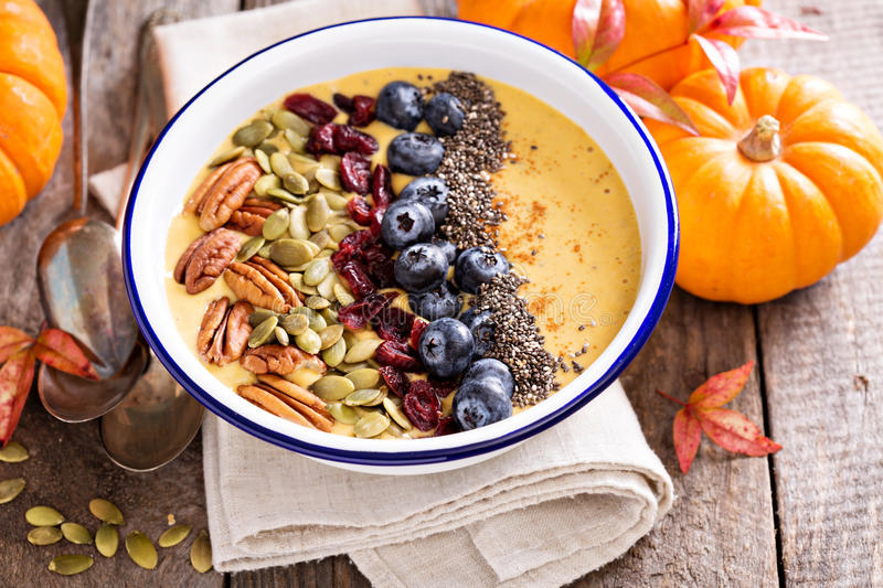 Pumpkin smoothie bowl with chia seeds, pecans, cranberries. And blueberries royalty free stock photography