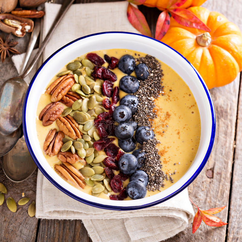 Pumpkin smoothie bowl with chia seeds, pecans, cranberries. And blueberries stock photography