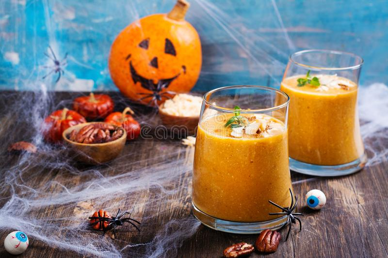 Pumpkin smoothie with coconut chips, cinnamon and mint. Halloween party treat on spooky background. Copy space stock photos