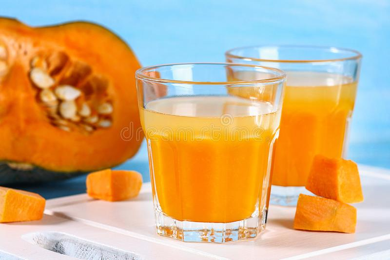 Pumpkin smoothie in glasses. Pumpkin juice on a blue table. Autumn drinks. stock photos