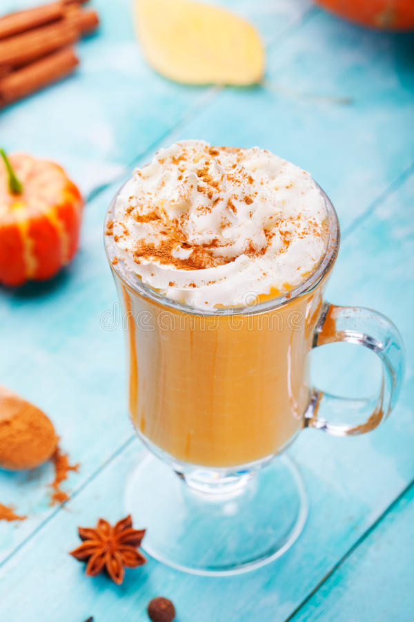 Pumpkin smoothie, spice latte with whipped cream. Turquoise wooden background. Pumpkin smoothie, spice latte with whipped cream on top on a turquoise wooden stock photo