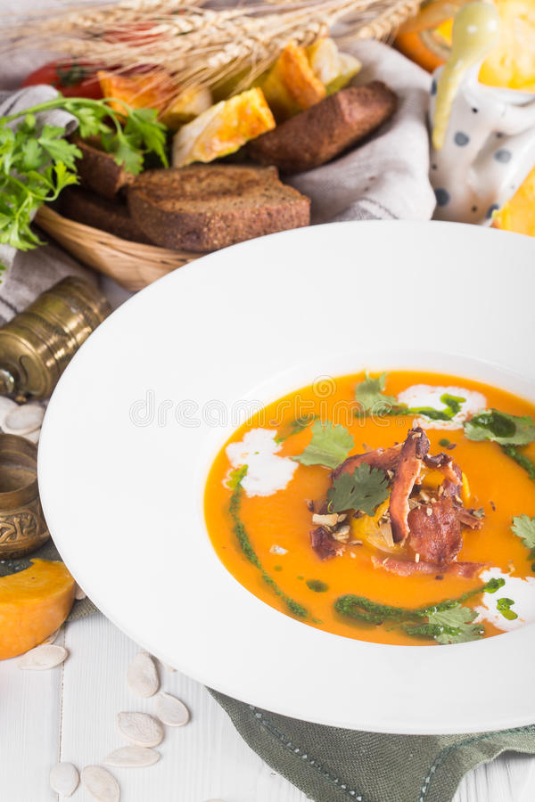 Pumpkin soup with bacon in a rustic style on the table. Bread and greens in the background stock images