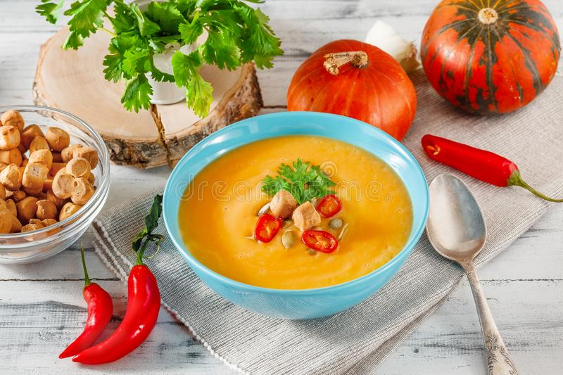 Spicy pumpkin soup with chili pepper in bowl stock photos