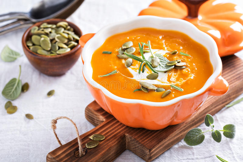 Pumpkin soup with cream, herbs and seeds royalty free stock images