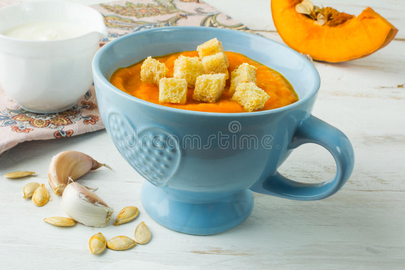 Pumpkin soup with croutons in a blue bowl stock photos