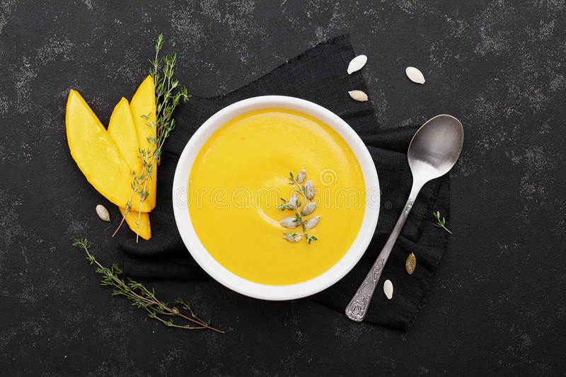 Pumpkin soup decorated seeds and thyme in white bowl on vintage black table top view. Flat lay styling. Pumpkin soup decorated seeds and thyme in white bowl on stock photos