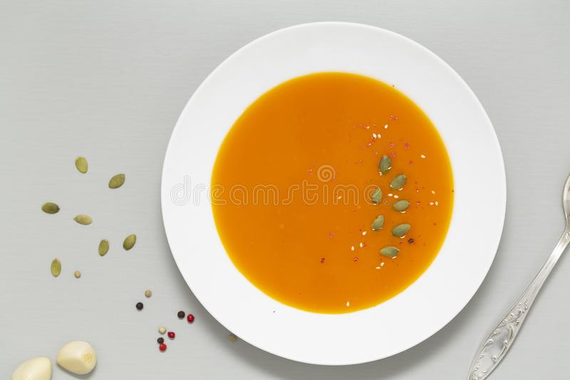 Pumpkin soup with herbs, cream and pumpkin seeds served in white bowl. Seasonal autumn food - Spicy pumpkin soup. stock photo